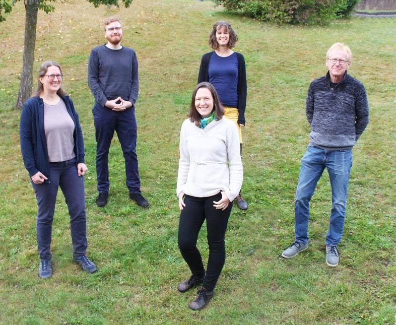 Das Team des Psychologischen Dienstes (v.l.n.r.): Christina Georgi, Dr. Simon Harbarth, Jana Schlee, Andres Ollefs und Dr. Werner Hecker (Leitung) haben sich auf einer Wiese im Corona-Abstand gruppiert
