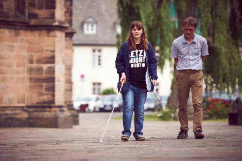 Eine Schülerin und ein Rehabilitationslehrer erkunden den Vorplatz der Elisabethkirche in Marburg