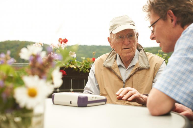 Beratungssituation eines älteren Menschen mit Seheinschränkungen