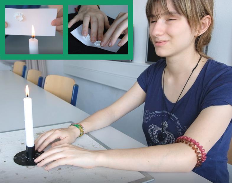 Eine Schülerin experimentiert mit einer Kerze.