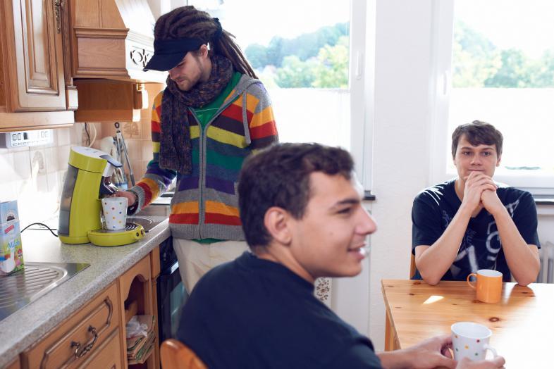 Drei junge Männer in einer WG-Küche beim Kaffeekochen