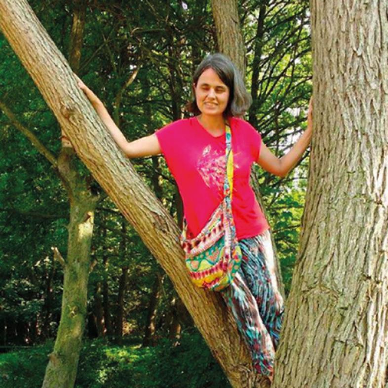 Unterricht im Freien: Eine Junge Frau steht in einer Astgabel