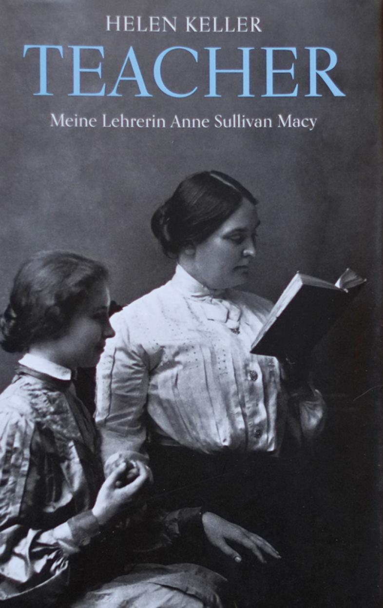 Das Cover des Buchs zeigt Anne Sullivan lesend, die junge Helen Keller sitzt zuhörend an ihrer Seite