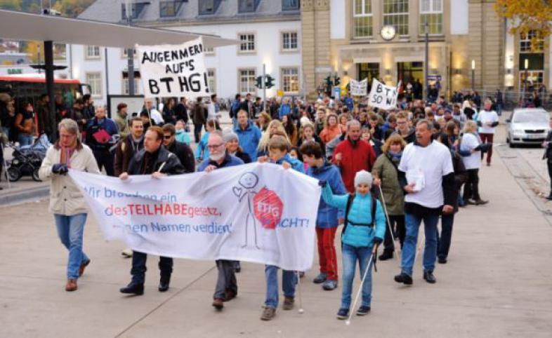 Der Demonstrationszug startet auf dem Vorplatz des Marburger Bahnhofs. Es sind mehrere Transparente zu sehen, die das BTHG kritisieren