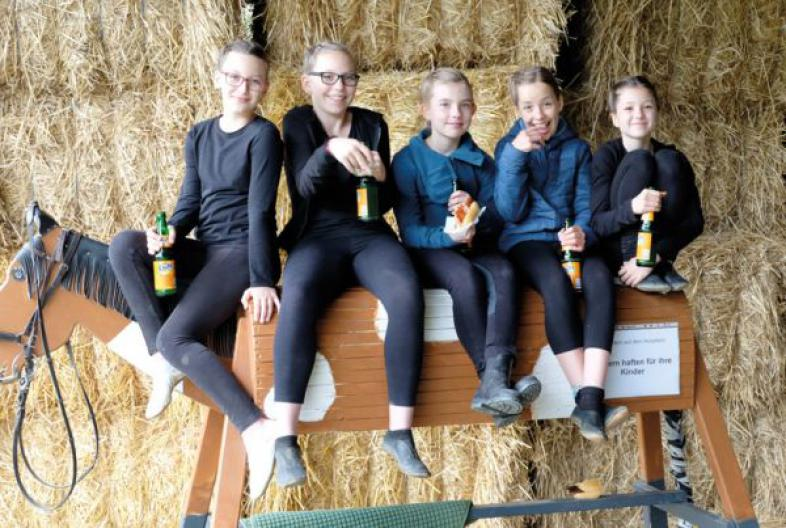 Fünf Schülerinnen und Schüler sitzen auf einem Holzpferd
