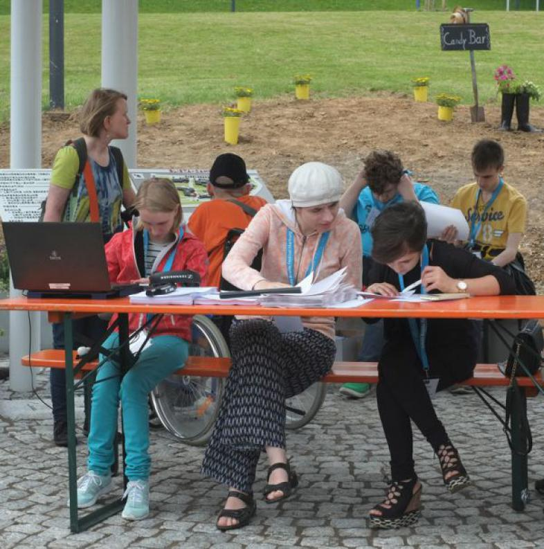 Drei Schülerinnen sitzen an einem Tisch, eine sitzt vor einem Laptop, sie sind das Empfangs- und Informationskomitee beim Ehemaligen Nachmittag