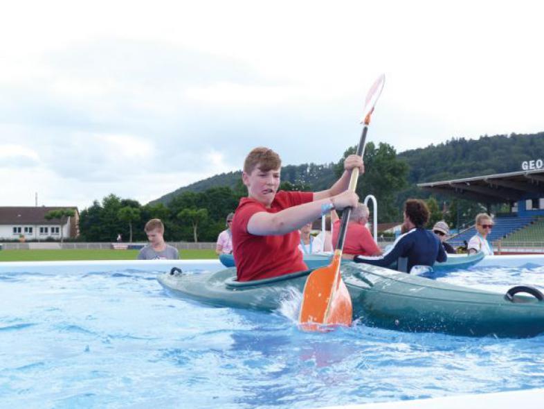 Ein junger Mann paddelt im mit Wasser gefüllten Pool, der eine Attraktion des Louis Braille Festivals war.