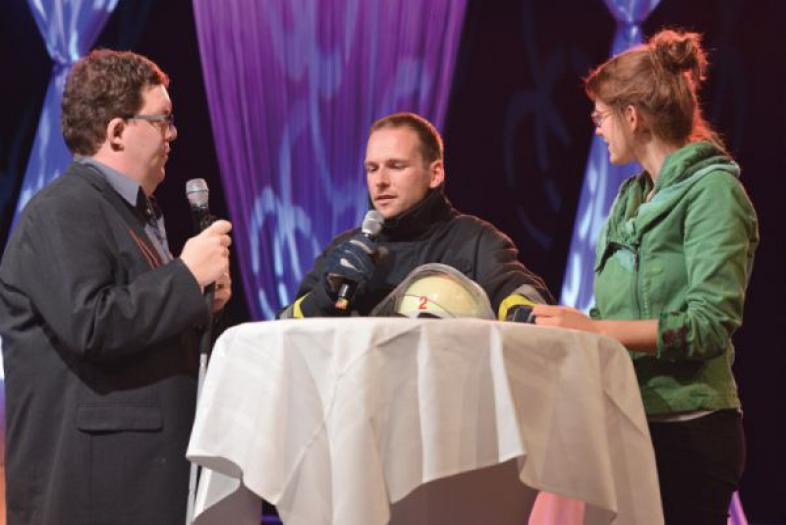 Sophia Neises und Thorsten Büchner interviewen Mirko Melz, der in der Kluft eines Feuerwehrmannes Rede und Antwort steht