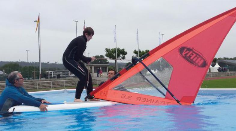 Lina-Sophie steht auf dem Surfbrett und versucht das Segel hoch zu ziehen, während Gerrit Arnold das Brett fest hält