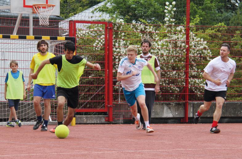 Ein Stürmer im gelben Trikot setzt sich gegen 2 Gegenspieler durch.