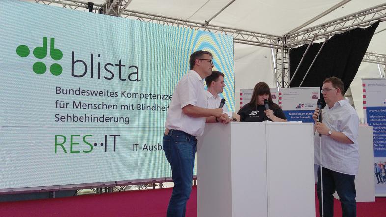 Talk-Runde vor Videowand: IT-Leiter Otfried Altfeld und 2 Auszubildende im Gespräch mit Thorsten Büchner