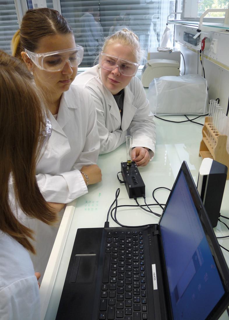 2 Schülerinnen sitzen am Labortisch und tragen Schutzbrillen