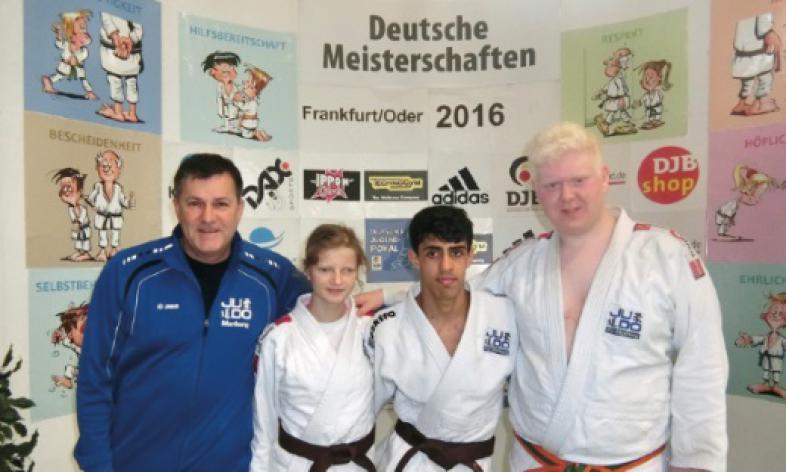 Gruppenfoto der drei erfolgreichen Judoka, links neben ihnen der Trainer