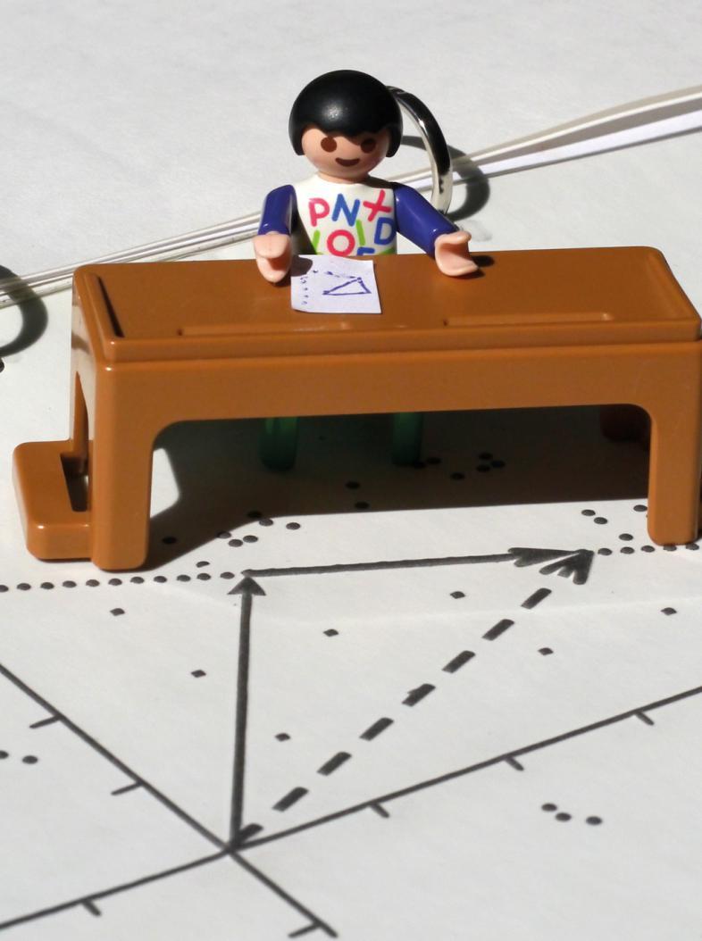 Eine Figur aus Playmobil sitzt an einem Schreibisch.