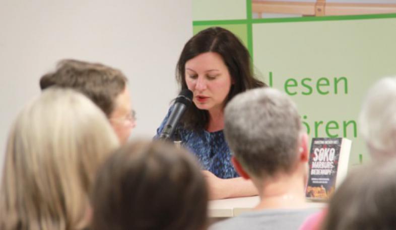 Christina Bacher liest aus ihrem Krimi, im Vordergrund die Zuhörer