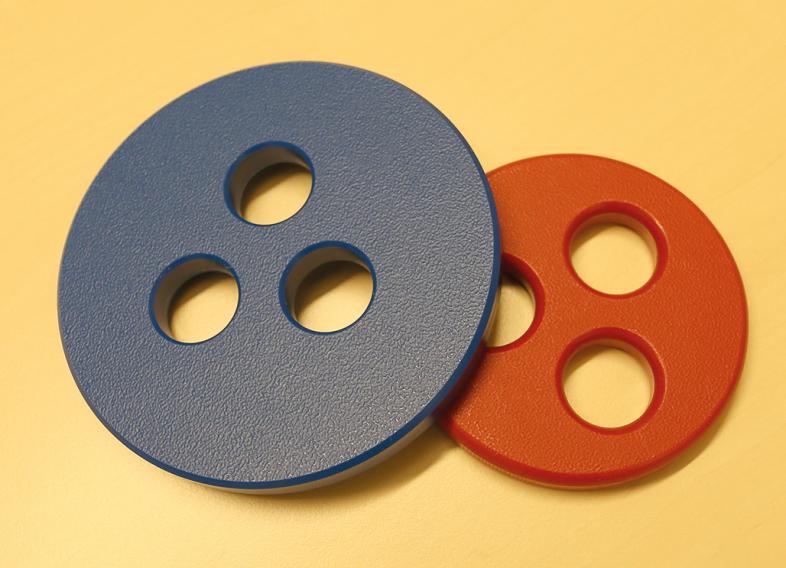 Zwei Scheiben mit jeweils drei Ausstanzungen. Dabei sind die Oberflächen an den Rändern unterschiedlich ausgearbeitet.