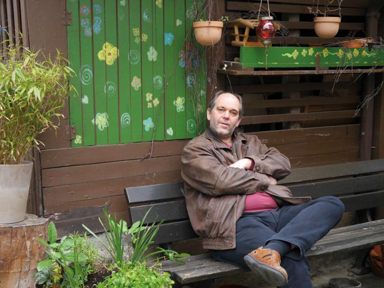 OMP sitzt auf einer Holzbank, er hat die Beine überschlagen und schaut zu dem Fotografen