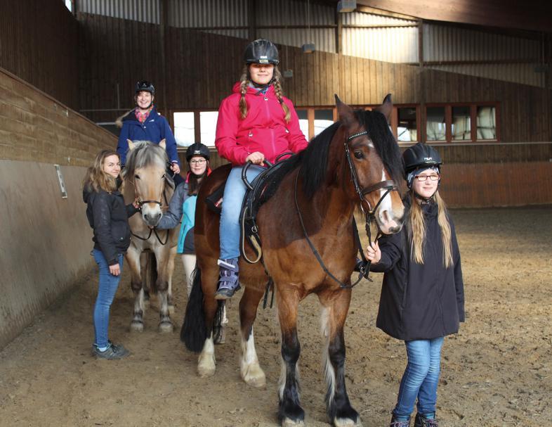 Zwei Mädchen reiten, zwei weitere führen die Pferde unter Aufsicht der Reitlehrerin durch die Halle