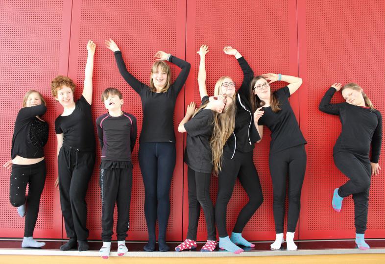 8 Mädchen spielen Theater, schwarz gekleidet stehen sie vor einer roten Wand