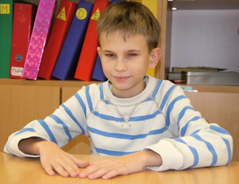 Till Zipprich, mit blau-weiß gestreiftem Pulli, sitzt am Tisch