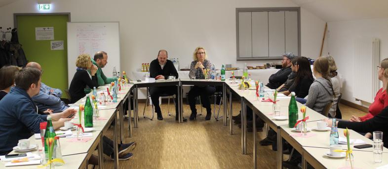 Die 2 Referenten und 12 Seminarteilnehmer sitzen an Tischen, die in U-Form aufgestellt sind.