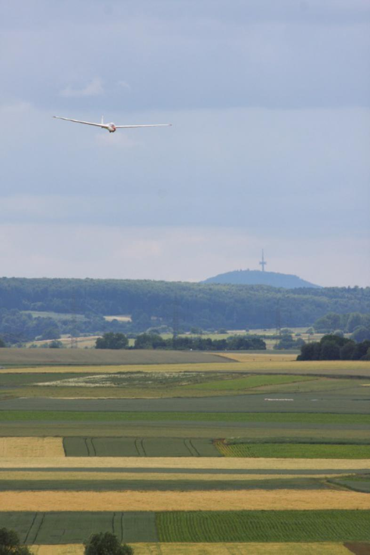Ein Segelflugzeug schwebt am Himmel über Wiesen, Feldern und Wäldern