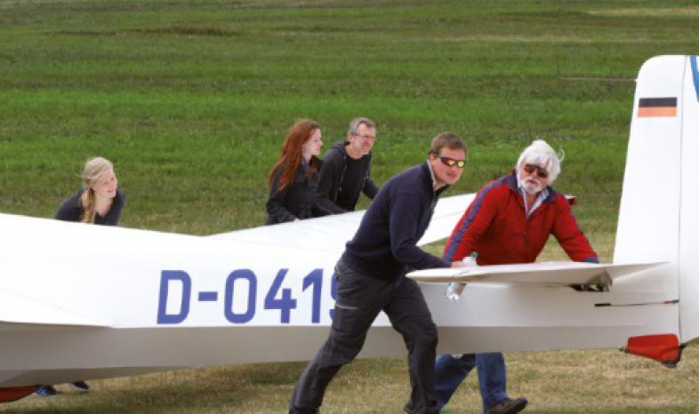 Fünf Personen schieben den Segelflieger