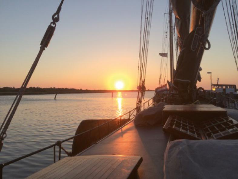 Blick auf das Deck des Segelschiffes, im Hintergrund geht die Sonne unter