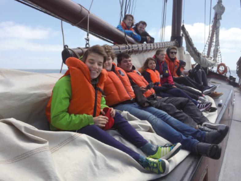 Sechs Schülerinnen und Schüler sitzen lachend, mit Schwimmwesten bekleidet, auf einem heruntergelassenen Segel, dahinter stehen eine Betreuerin und ein Betreuer