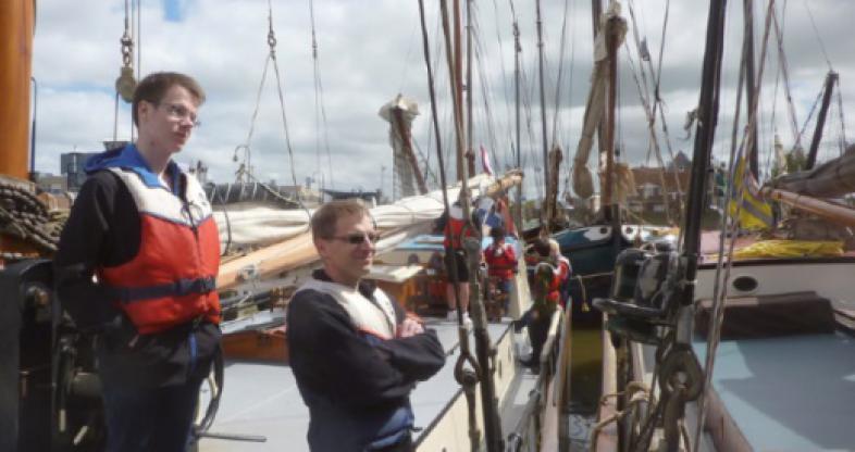 Die Gruppe tummelt sich an Deck ihres Segelschiffes im Hafen, im Vordergrund stehen zwei junge Männer