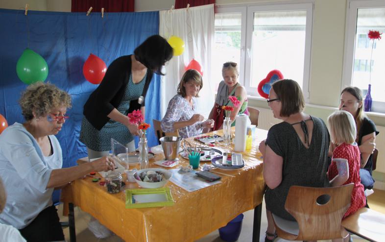 An einem Tisch werden Besucher zu künstlerischen Experimenten eingeladen
