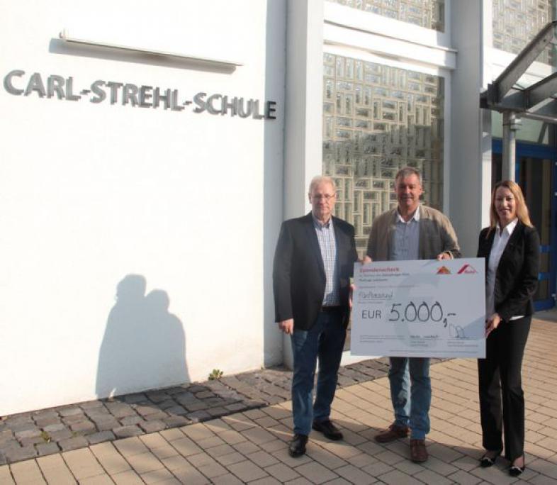 Vor dem Eingang der CSS stehen Ulrike Weikart, Joachim Lembke und Manfred Martin. Schulleiter Lembke hält einen überdimensionierten Scheck über 5000 €.