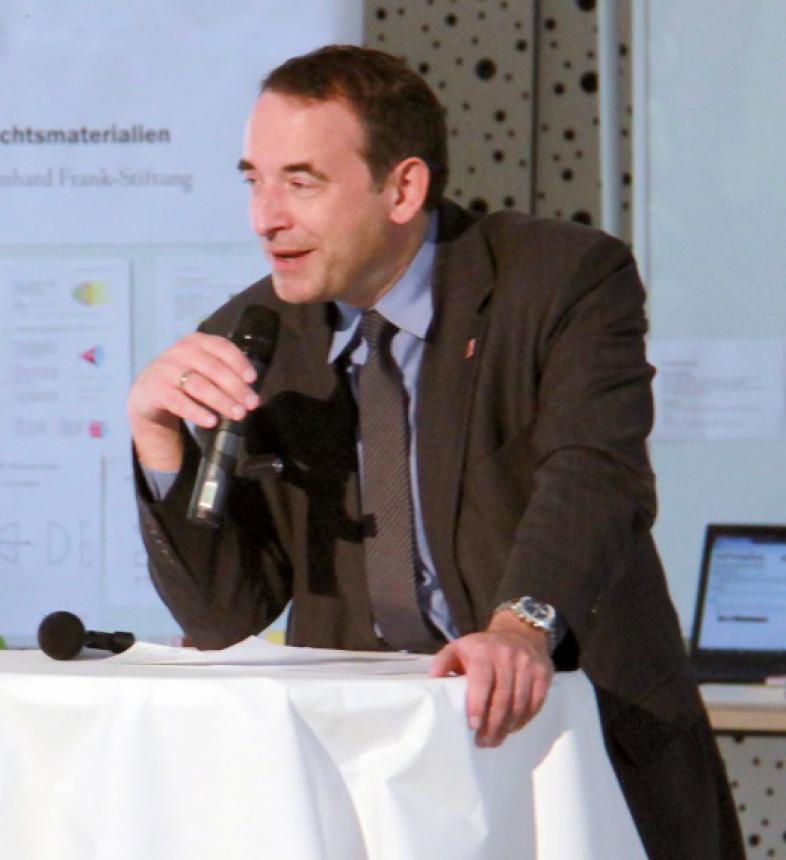 Kultusminister Alexander Lorz mit Mikrofon an einem Stehtisch