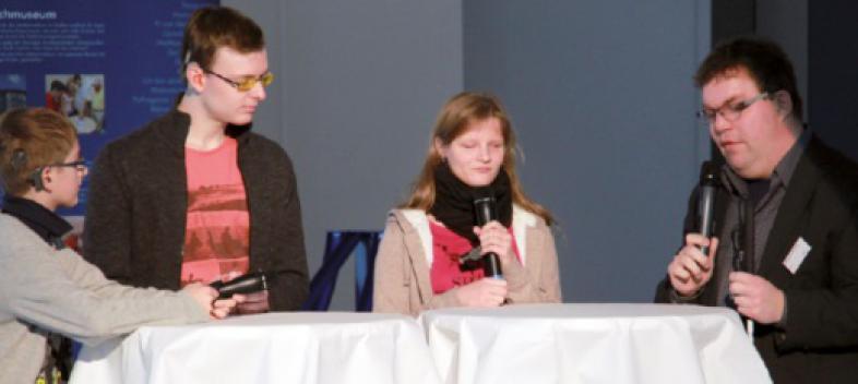 Matthias, Tizian und Tabea stehen während der Podiumsdiskussion neben Thorsten Büchner an zwei Stehtischen