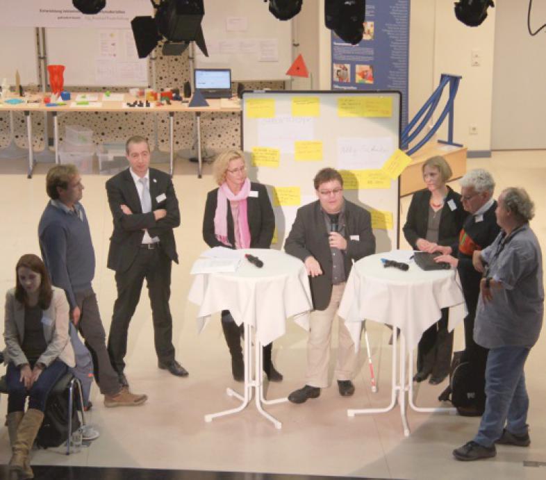 Sechs Vertreter von Selbsthilfe-, Eltern- und Pädagogenverbänden stehen während der Talkrunde im Kreis, Thorsten Büchner moderiert mit Mikrofon Im Vordergrund sitzt eine Gebärdendolmetscherin