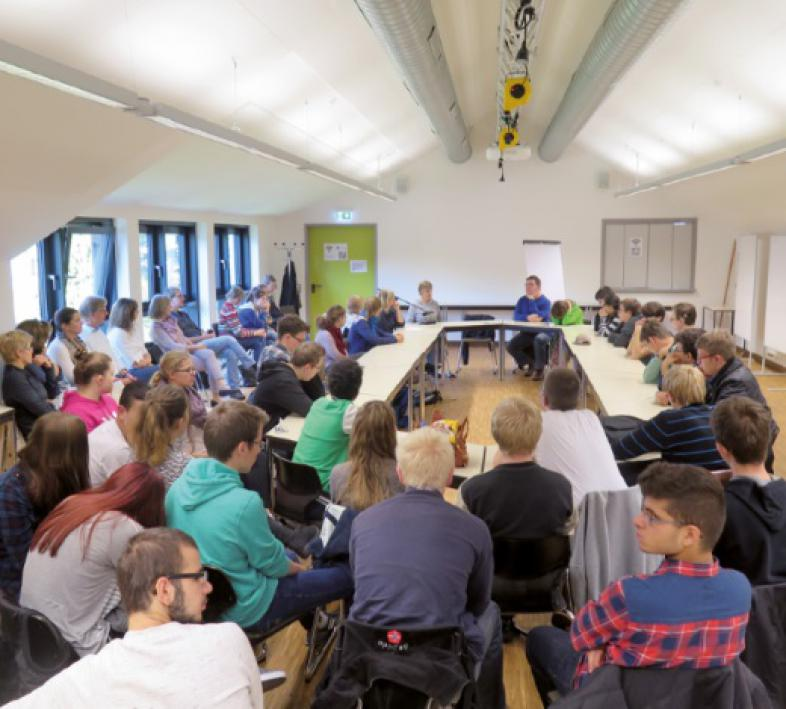 Sabriye Tenberken sitzt bei ihrem Vortrag im Konferenzraum am Tisch, umgeben von einer großen Anzahl Schülerinnen und Schülern