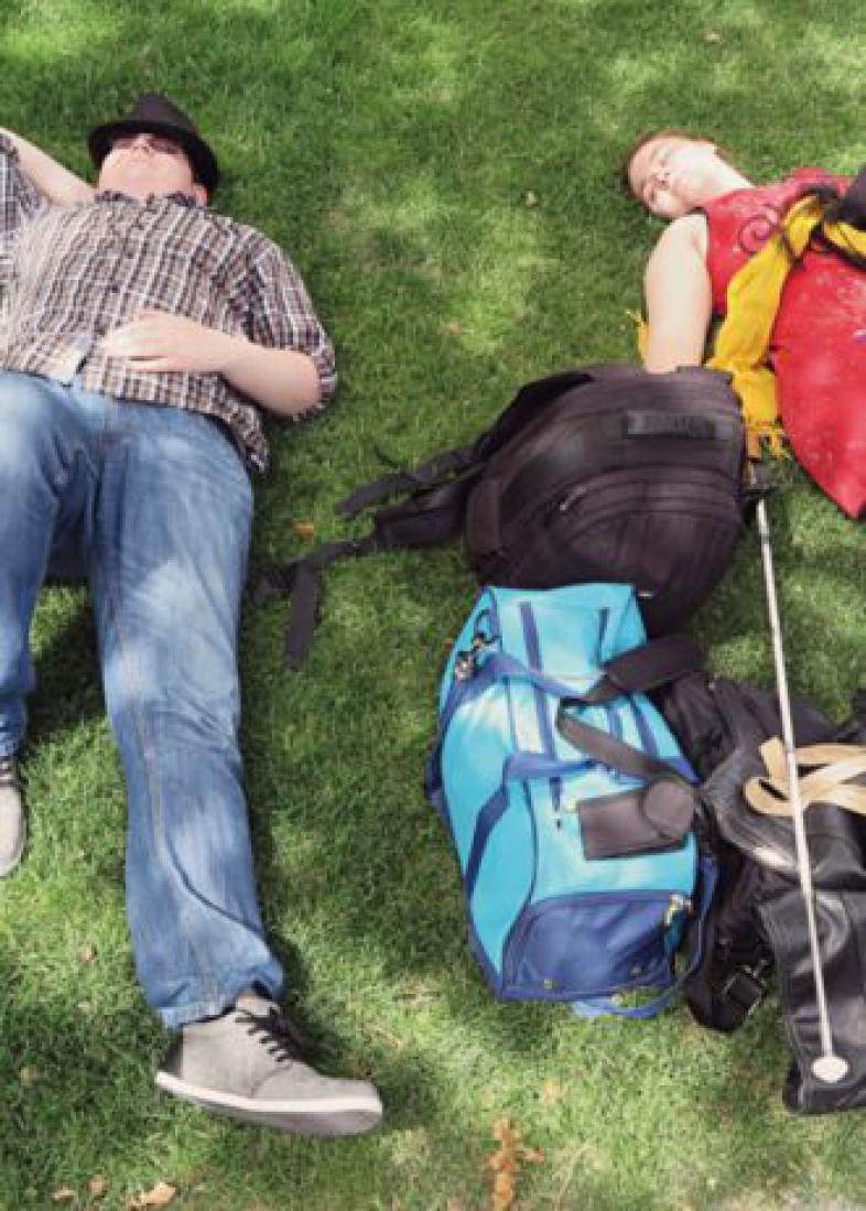 Eine Schülerin und ein Schüler liegen im Gras unter einem Baum und dösen vor sich hin. Zwischen ihnen sind verschiedene Gepäckstücke und ein Langstock.