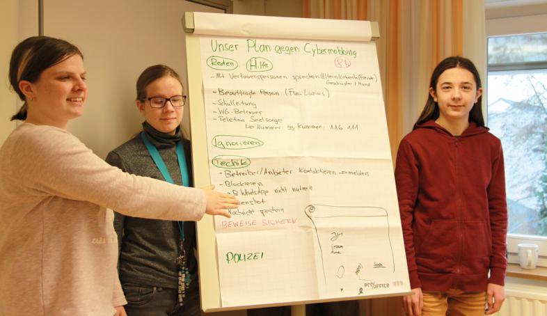 Drei Schülerinnen stehen neben einem Flipchart, auf dem die Regeln gegen Cybermobbing notiert sind.