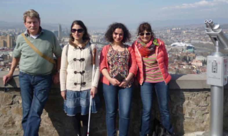 Gruppenfoto vor einer Mauer, im Hintergrund die Stadt Tbilisi