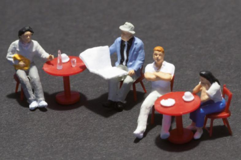 Eine Gruppe, bestehend aus vier kleinen Puppen, sitzt an zwei Kaffeehaustischen