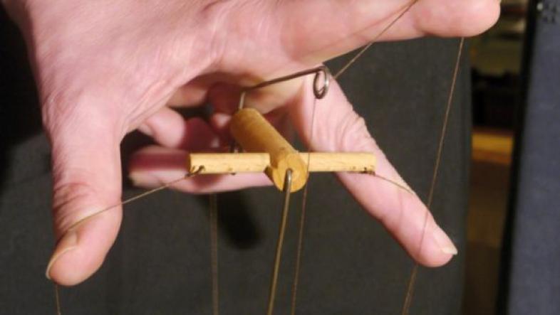 Eine Hand zieht die Fäden bei einer Marionetten-Puppe