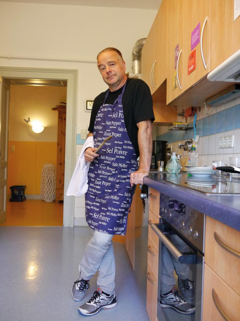 Der Autor steht - bekleidet mit einer violetten Schürze - in der Küche einer blista-Wohngruppe.