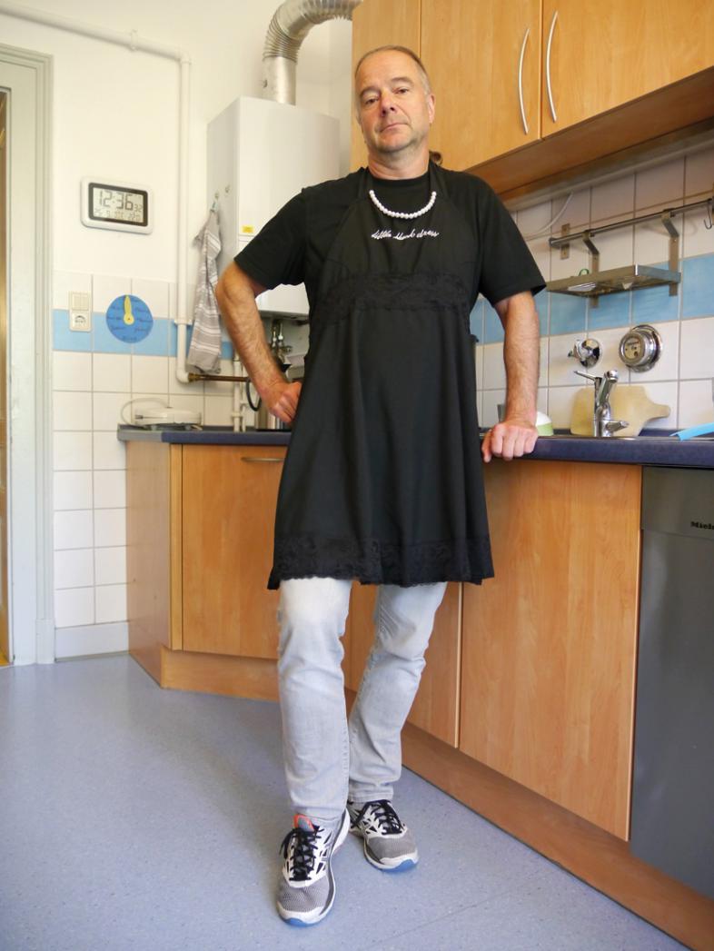 Der Autor steht - bekleidet mit einer schwarzen Schürze - in der Küche einer blista-Wohngruppe.