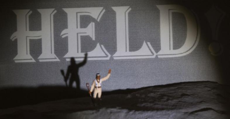 """Eine kleine Indianer-Puppe steht mit ausgestreckten Arm und Gewehr vor dem Schriftzug """"HELD"""""""