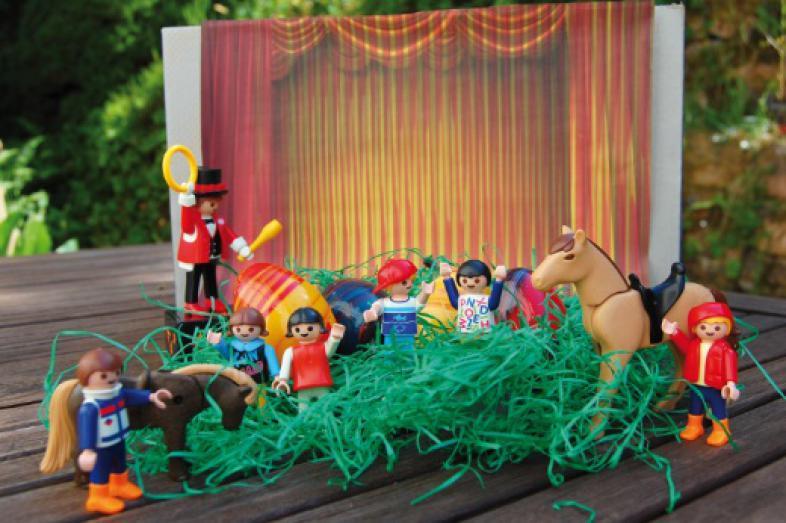 Playmobilmännchen mit Pferden und einem Zirkusdirektor stehen auf Ostergras vor einer kleinen Bühne