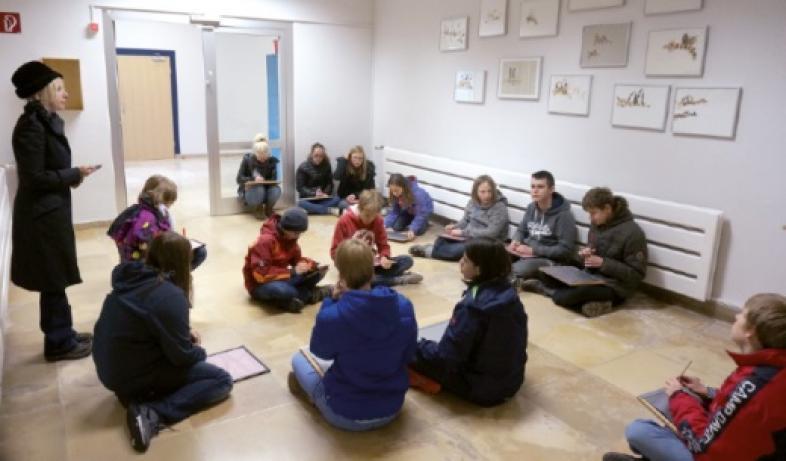 Schülerinnen und Schüler sitzen auf dem Boden, Mirja Wellmann steht vor ihnen
