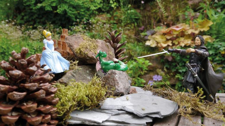 Das Foto zeigt eine Spielfigurenszene: Ein Ritter bekämpft einen Drachen, das schöne Fräulein beobachtet im Hintergrund