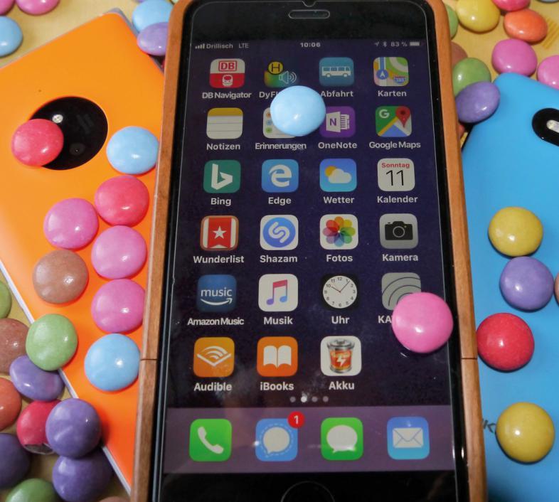 Das Bild zeigt übereinanderliegende Smartphones, das Display zeigt verschiedene Apps. Auf und neben den Smartphones liegen viele bunte Smarties.