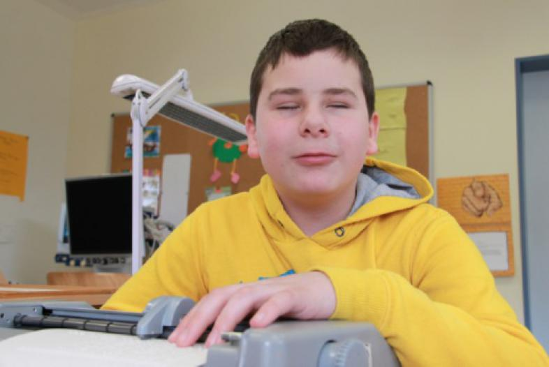 Ein Junge schreibt auf der Punktschriftmaschine