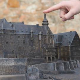 Eine Hand zeigt mit dem Zeigefinger auf das taktile Marburger Schloss-Modell